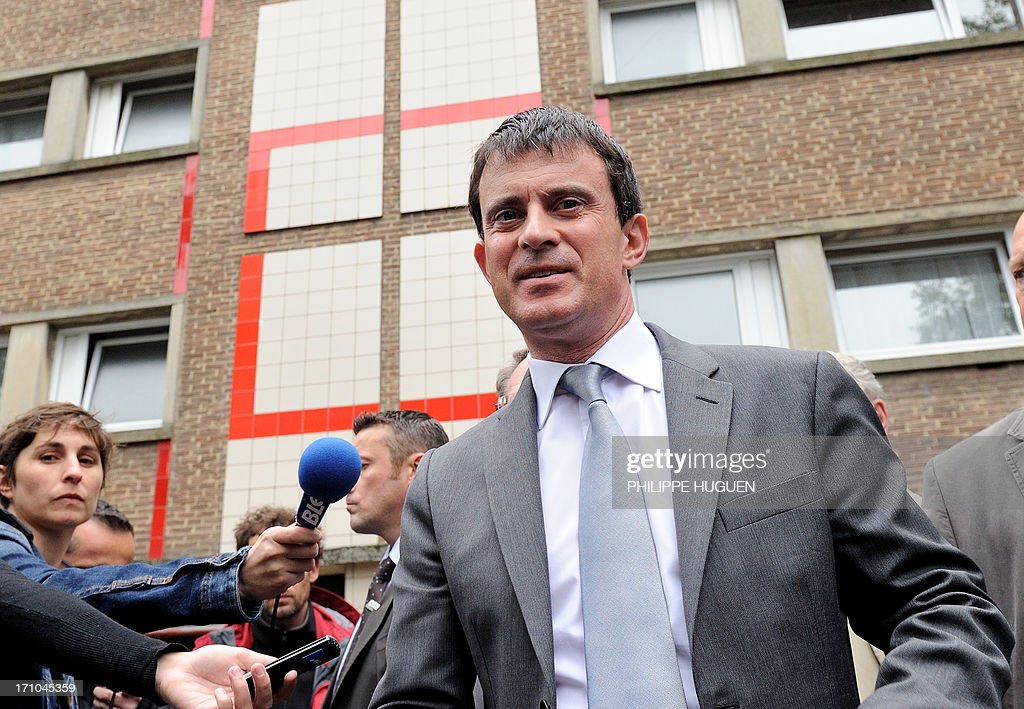 French Interior Minister Manuel Valls looks on during a visit to a priority area of critical security (ZSP) at the Mousserie district in Wattrelos, northern France on June 21, 2013.