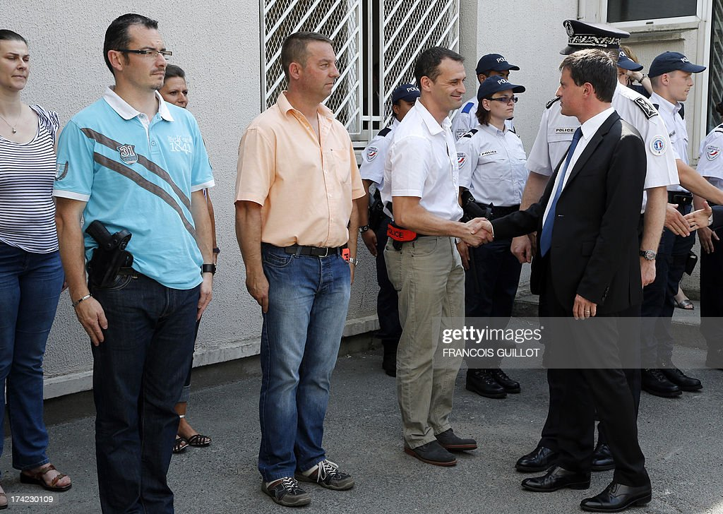 French Interior Minister Manuel Valls (R) meets police officers during a visit at a police station in Trappes, a suburb of Paris, on July 22, 2013. Violent clashes erupted between citizens and French police near Trappes' police station late on July 18, 2013, after police officers carried out an identity check on a full-face veiled woman and her husband. The woman's husband tried to strangle one of the officers during the check according to Versailles' prosecutor Vincent Leclous on July 20. The situation was still tense in front of the police station on the evening of July 21, where a group of people challenged the police before being dispersed by backup units.