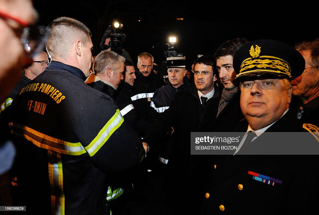 French Interior Minister Manuel Valls (3rd R), Mulhouse's Mayor Jean Rottner (2nd R) and Haut-Rhin Prefect Alain Perret (R) meet firemen at Les Coteaux, a district of Mulhouse, on January 10, 2013. The district of 'Les Coteaux ' is one of 49 'Zone de Sécurité Prioritaire' (ZSP) ('Priority Security Zones') where the fight against criminality and violence are a major issue. Many cars were burnt in the district during the new year's celebration on December 31, 2012, and youths threw a few Molotov cocktails at a tramway on January 5, 2013. AFP PHOTO / SEBASTIEN BOZON