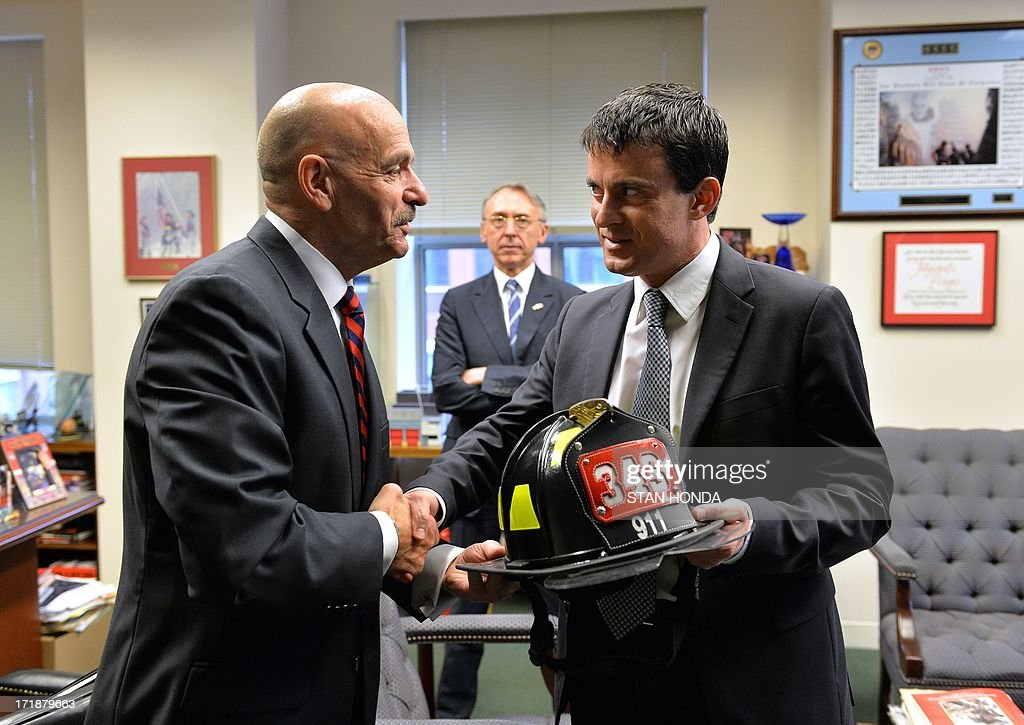 French Interior Minister Manuel Valls (R) receives a firefighter helmet from New York City Fire Department Commissioner Salvatore Cassano (L) before a briefing on the September 11, 2001 attacks on the World Trade Center June 29, 2013 at fire department headquarters in the Brooklyn borough of New York. The firefighter helmet represents the 343 firefighters lost in the attacks on 9/11. AFP PHOTO/Stan HONDA