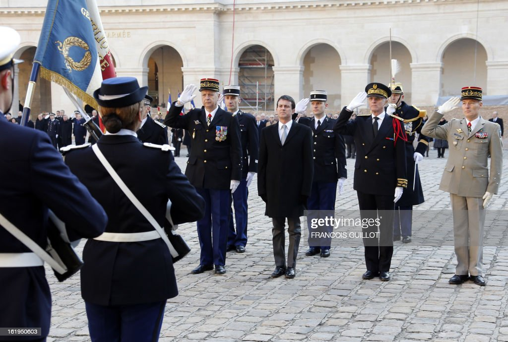 French Interior minister Manuel Valls (C) reviews a unit of the French Gendamerie during a memorial cemerony honoring gendarmes who died during service, on February 18, 2013 at the Hotel des Invalides in Paris. AFP PHOTO / FRANCOIS GUILLOT