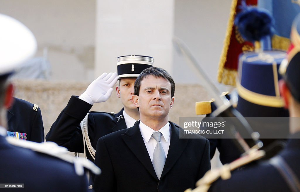 French Interior minister Manuel Valls (C) reviews a unit of the French Gendarmerie during a memorial cemerony honoring gendarmes who died during service, on February 18, 2013 at the Hotel des Invalides in Paris.