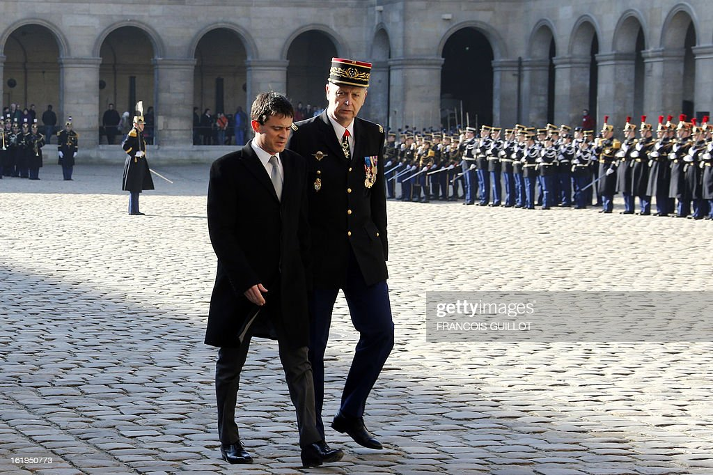 French Interior minister Manuel Valls (L) reviews a unit of the French Gendarmerie during a memorial cemerony honoring gendarmes who died during service, on February 18, 2013 at the Hotel des Invalides in Paris. AFP PHOTO / FRANCOIS GUILLOT