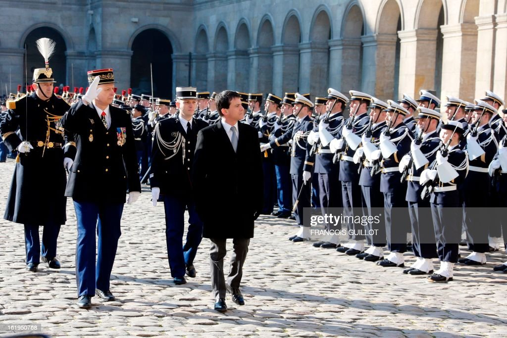 French Interior minister Manuel Valls (C) reviews units of the French Gendarmerie during a memorial cemerony honoring gendarmes who died during service, on February 18, 2013 at the Hotel des Invalides in Paris.
