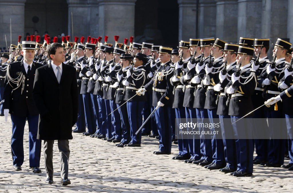 French Interior minister Manuel Valls (2L) reviews units of the French Gendarmerie during a memorial cemerony honoring gendarmes who died during service, on February 18, 2013 at the Hotel des Invalides in Paris.