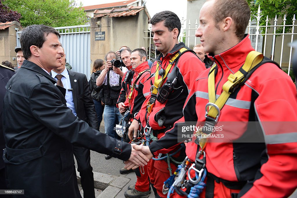 French interior minister Manuel Valls (L) shakes hand with fire brigades in front of an abandoned factory that was housing nearly 300 Roma squatters, which went on fire overnight, killing at least three people on May 13, 2013, in Lyon,eastern France.