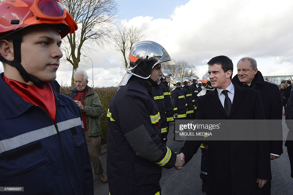 French Interior minister Manuel Valls (2nd R) shakes hands with a firefighter as he visits a fire station in Magny-en-Vexin, 60 kms northeast of Paris, on February 21, 2014.