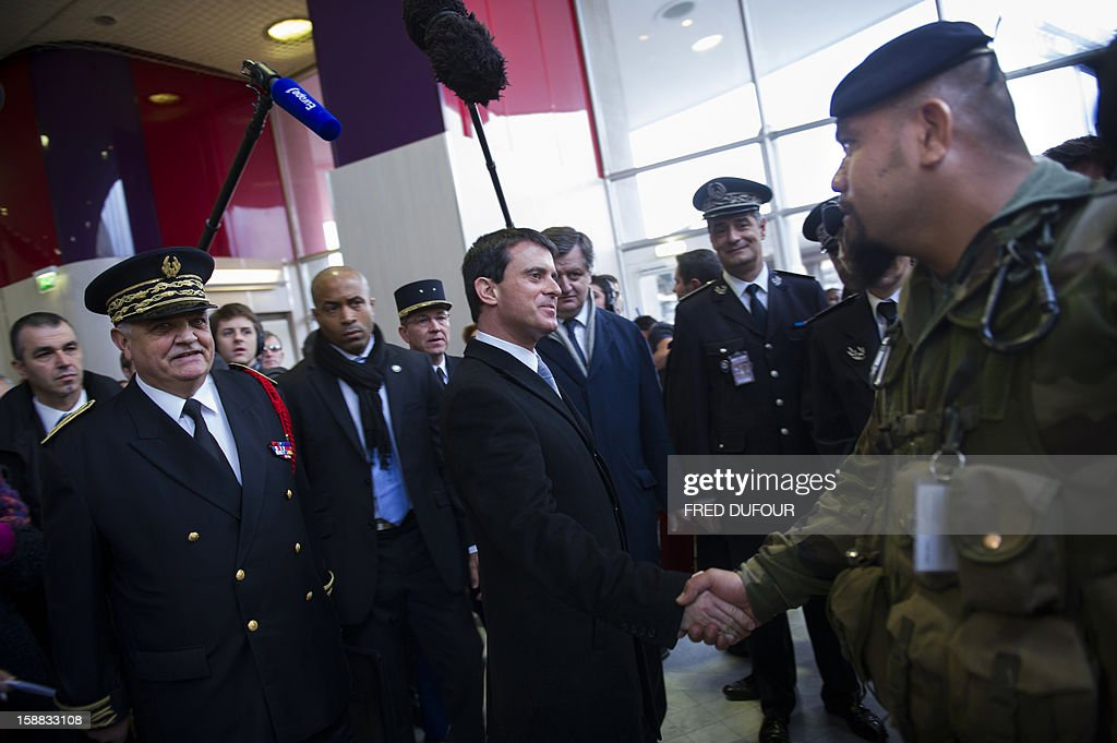 French Interior Minister Manuel Valls (C) shakes hands with a soldier in charge of security at the Charles de Gaulle airport on December 31, 2012 in Roissy during a visit with Seine Saint-Denis Prefect Christian Lambert (L).