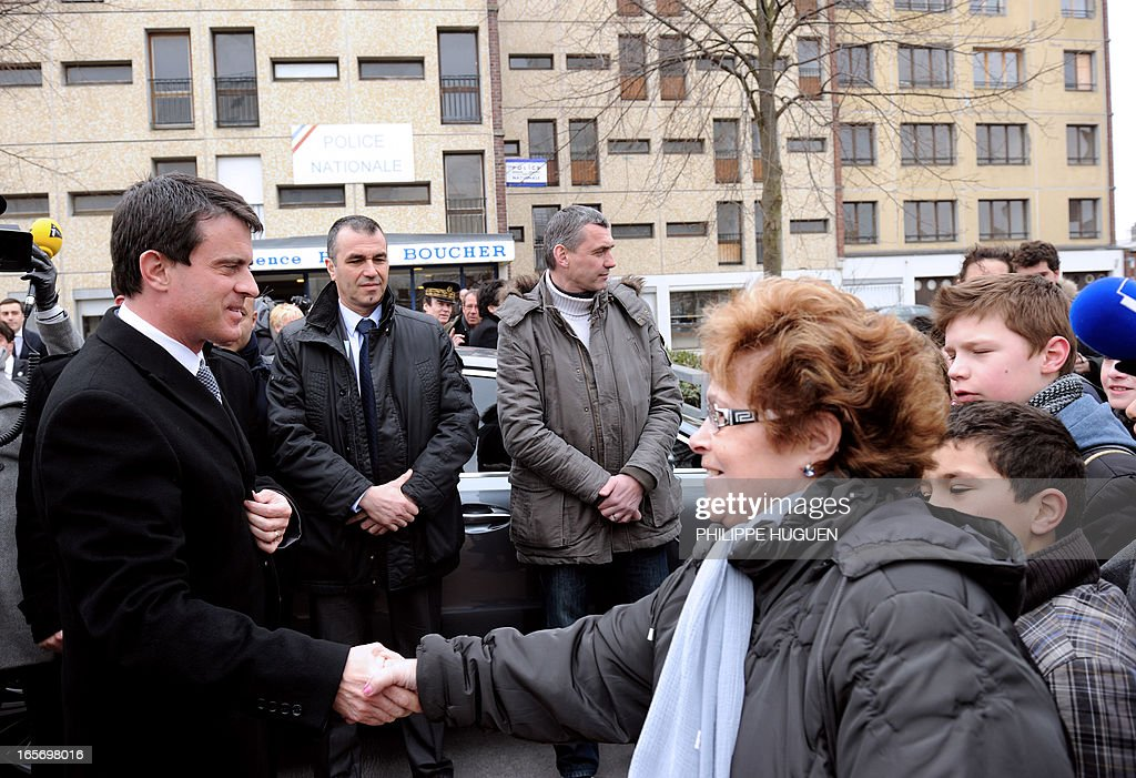 French Interior Minister Manuel Valls (L) shakes hands with a woman as he meets local residents of the 'Amiens Nord' classified security priority zone (ZSP) on April 5, 2013 during his visit in Amiens, northern France.