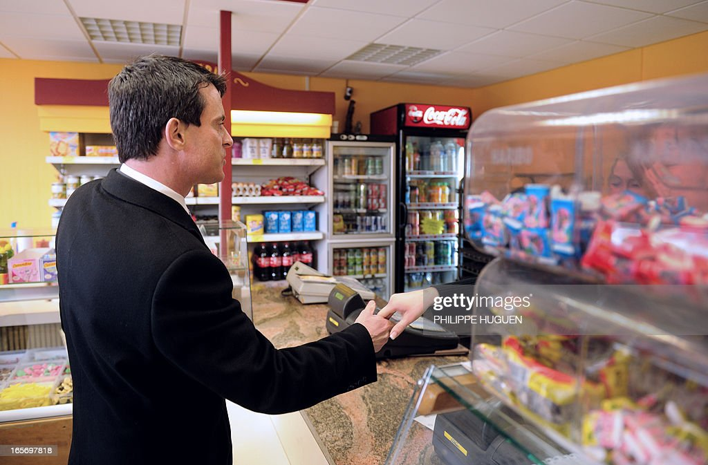 French Interior Minister Manuel Valls (L) shakes hands with an employee in a bakery in the 'Amiens Nord' classified security priority zone (ZSP) on April 5, 2013 during his visit in Amiens, northern France.