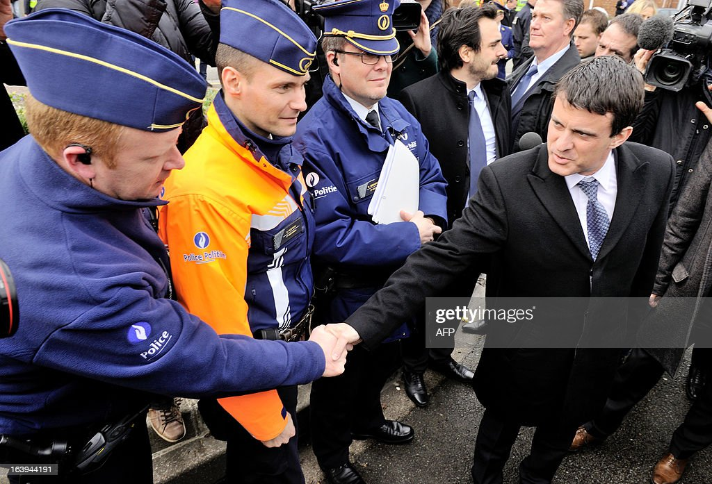 French Interior Minister Manuel Valls (R) shakes hands with Belgian police officers as he attends a road traffic control on March 18, 2013 near the border in Tourcoing, northern France, as part of a Franco-Belgian cooperation agreement between police and customs. AFP PHOTO PHILIPPE HUGUEN