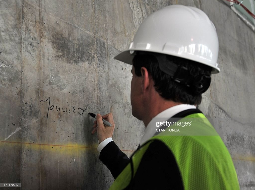French Interior Minister Manuel Valls signs his name on an unfinished wall on the 24th floor of One World Trade Center after he visited the 9-11 Memorial at Ground Zero June 29, 2013 in New York. AFP PHOTO/Stan HONDA