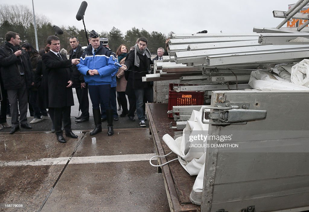 French Interior Minister Manuel Valls speaks with a French gendarme on December 28, 2012 at the Fleury-en-Bière's toll, during a visit focused on road safety. AFP PHOTO/JACQUES DEMARTHON