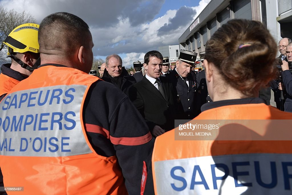 French Interior minister Manuel Valls (C) speaks with firefighters as he visits a fire station in Magny-en-Vexin, 60 kms northeast of Paris, on February 21, 2014.