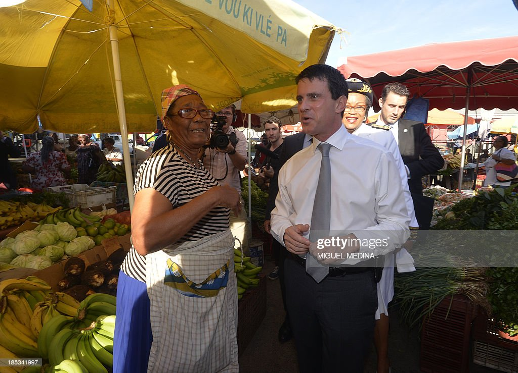 French Interior minister Manuel Valls (C) talks to a woman as he visits a market in Pointe-a-Pitre on the French Caribbean island of Guadeloupe on October 18, 2013. Valls, on a four-day visit to the French caribbean islands, facing an explosion of crime, decided to come back to Paris earlier than scheduled to receive a report on the detention of Leonarda, a 15-year-old Roma girl, during a school trip and her subsequent deportation to Kosovo that has shaken France.