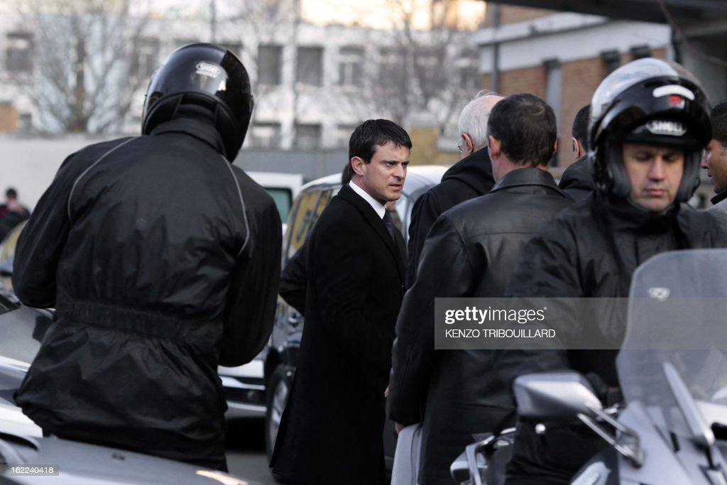 French Interior minister Manuel Valls (C) talks to journalists on February 21, 2013 in Paris, after an accident following a car chase between policemen and suspects driving a SUV vehicle, killing two policemen earlier in the morning at the Porte de la Chapelle. AFP PHOTO KENZO TRIBOUILLARD