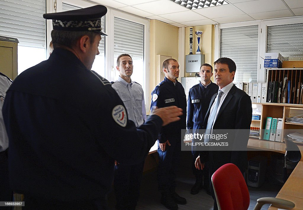 French Interior Minister Manuel Valls (R) talks with police officers on May 17, 2013 in Annemasse as he visits a police station in a priority areas of critical security (ZSP). AFP PHOTO/PHILIPPE DESMAZES