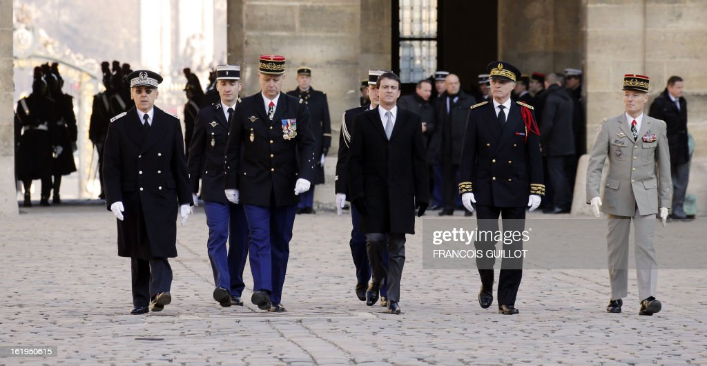 French Interior minister Manuel Valls (C) walks during a memorial cemerony honoring French gendarmes who died during service, on February 18, 2013 at the Hotel des Invalides in Paris.