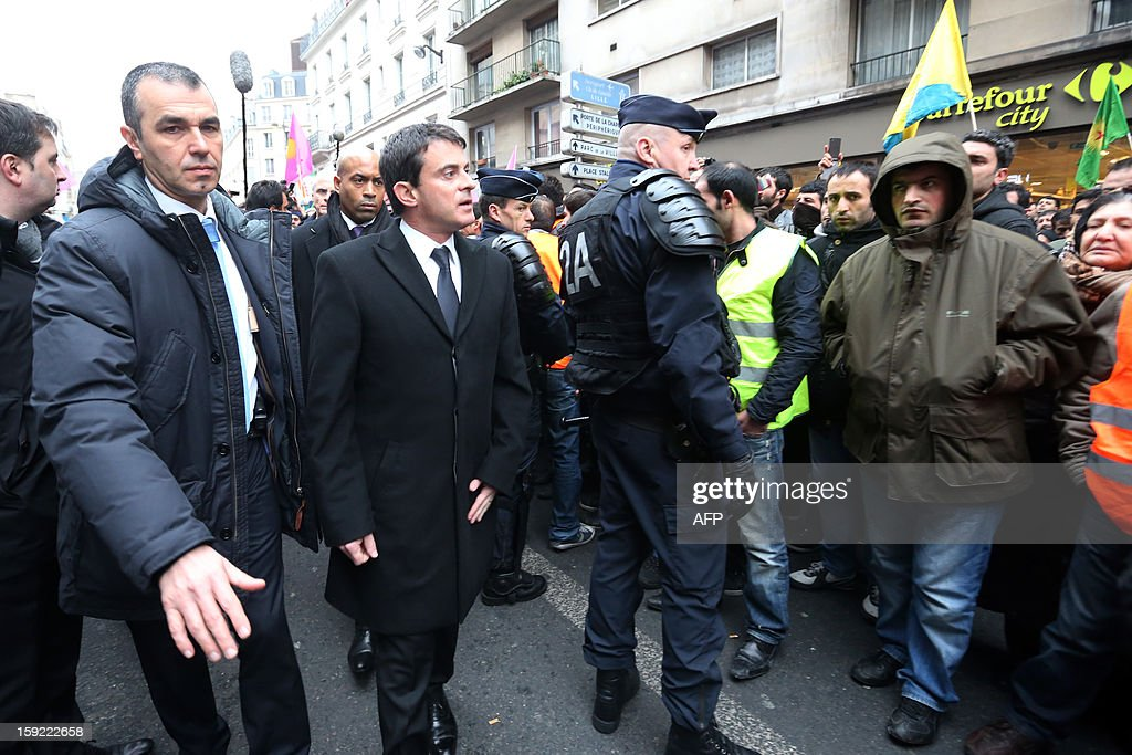 French Interior Minister Manuel Valls (2nd-L) walks while members of the Kurdish community in France protest near the Kurdistan Information Bureau on January 10, 2013 in Paris, where three Kurdish women were found killed with a gunshot to the head. The bodies of the women were found shortly before 2:00 am (0100 GMT) inside the building in the 10th arrondissement of the French capital. One of the women was 32-year-old Fidan Dogan who worked in the institute's information centre, according to its director, Leon Edart. The identities of the other two women, who were reportedly Kurdish activists but did not work at the Institute, were not immediately available. AFP PHOTO / THOMAS SAMSON