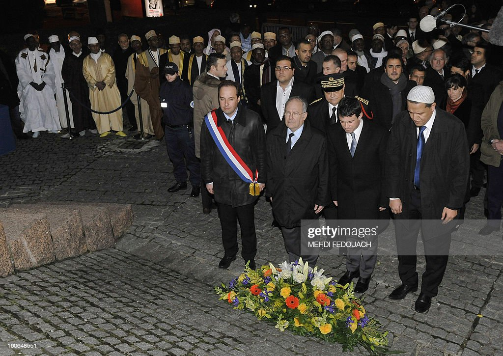French Interior ministry Manuel Valls (C) and Drancy's imam Hassen Chalghoumi spend some moment in silence, on February 4, 2013 in front of Drancy's Shoah memorial, outside Paris, during a rally of several imams to pay tribute to Jewish victims of the Nazis.