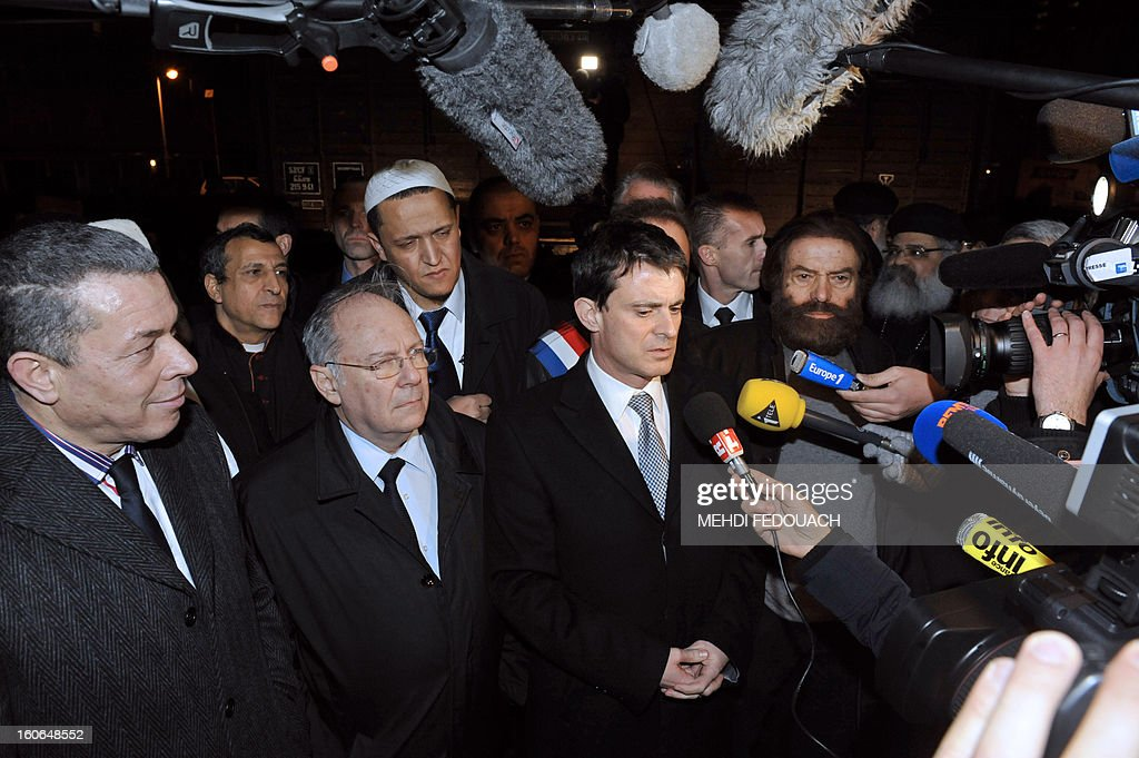 French Interior ministry Manuel Valls (C) answers journalists' questions, on February 4, 2013 at Drancy's Shoah memorial, outside Paris, during a rally of several imams to pay tribute to Jewish victims of the Nazis.