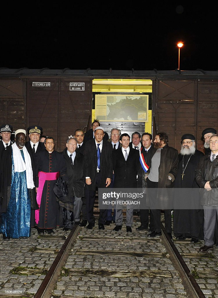 French Interior ministry Manuel Valls (C) poses next to Drancy's imam Hassen Chalghoumi and other imams, on February 4, 2013 at Drancy's Shoah memorial, outside Paris, during a rally of imams to pay tribute to Jewish victims of the Nazis.