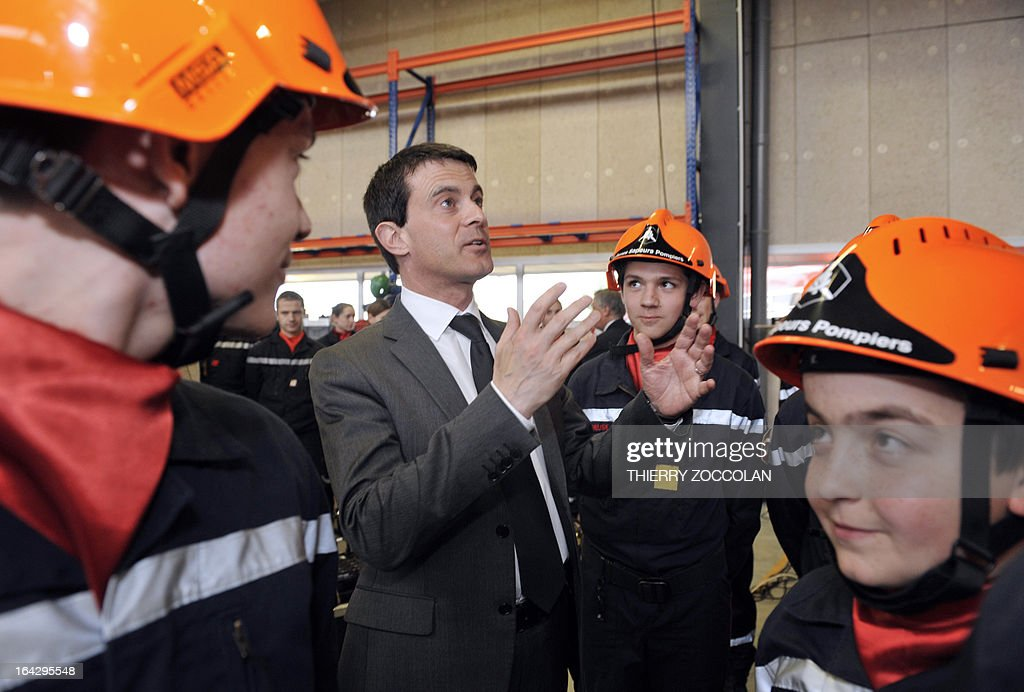 French Interior Minsiter Manuel Valls (C) reacts beside young children wearing firefighter uniforms on March 22, 2013, during the inauguration of the Maurice Lebon Emergency Centre in Gueret, central France, after signing an agreement organizing local emergency and rescue services SAMU and SDIS of the Creuse department.