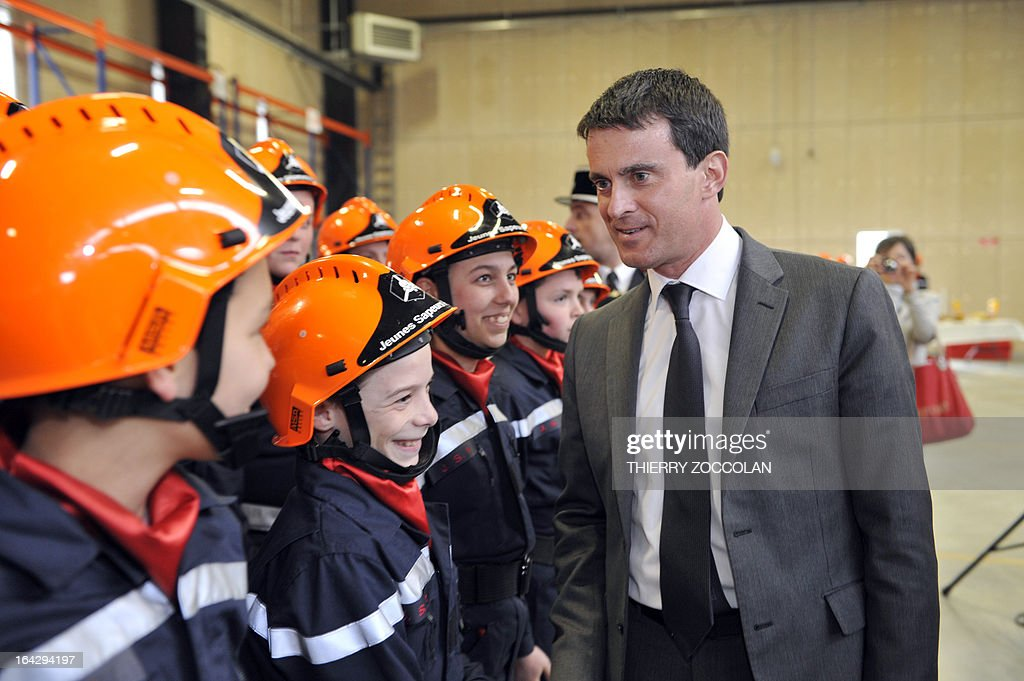 French Interior Minsiter Manuel Valls (C) reviews young children wearing firefighter uniforms on March 22, 2013, during the inauguration of the Maurice Lebon Emergency Centre in Gueret, central France, after signing an agreement organizing local emergency and rescue services SAMU and SDIS of the Creuse department. AFP PHOTO THIERRY ZOCCOLAN