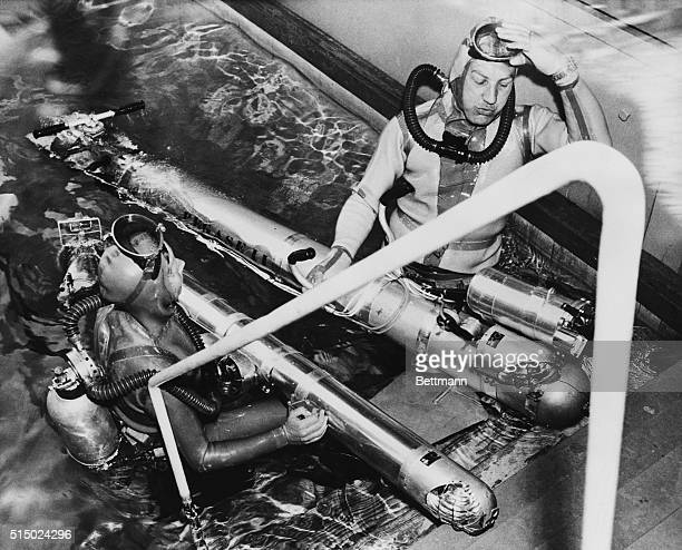 French inventor Dimitri Rebikoff with assistance from his wife Ada demonstrates his Pegasus underwater vehicle in the Piscine Deligny swimming pool...