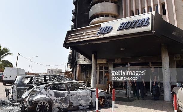 French investigators stand in front of the Splendid hotel on January 17 2016 in Ouagadougou following a jihadist attack by AlQaeda linked gunmen late...