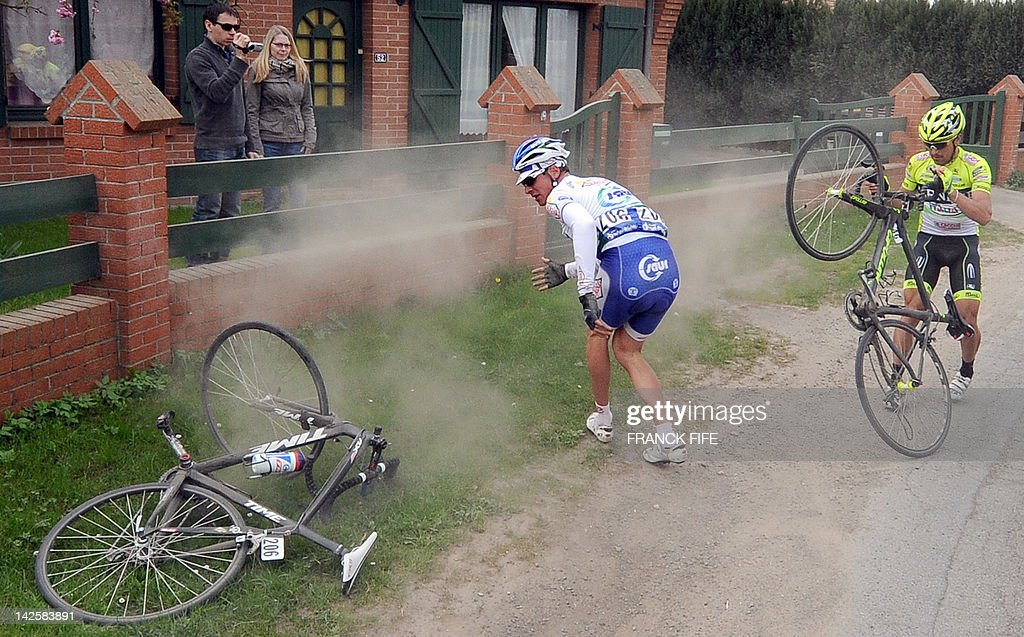 French Jean Lou Pajani (L-Team Francaise des Jeux) and Italian Oscar Gatto are pictured after they felt on a cobblestoned road during the 110th edition of the Paris-Roubaix one-day classic cycling race, on April 8, 2012, in Roubaix, northern France. Boonen, who had previously won in 2005, 2008 and 2009, equals the record of wins in Paris-Roubaix held by compatriot Roger De Vlaeminck. Boonen won the race ahead of French Sebastien Turgot (Team Europcar) and Italian Alessandro Ballan (Team BMC). AFP PHOTO / FRANCK FIFE