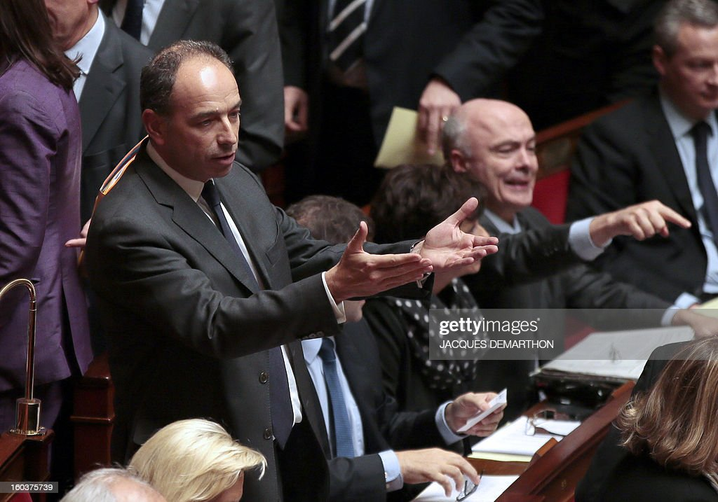French Jean-Francois Cope (L), head of France's right-wing UMP opposition party, reacts during a session of questions to the government at the National Assembly on January 30, 2013 in Paris. AFP PHOTO / JACQUES DEMARTHON
