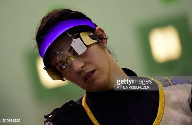French Jennifer Olry pushes her neck prior to the qualification round of 10m air rifle category for women in AUDI Arena of Gyor on February 26 2016...