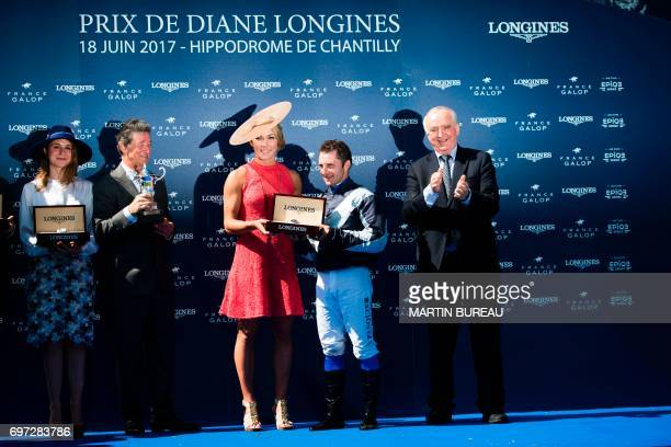 French jockey Stephane Pasquier smiles as he receives the trophy by US skier Mikaela Shiffrin after winning the Prix de Diane a 2100meters flat horse...