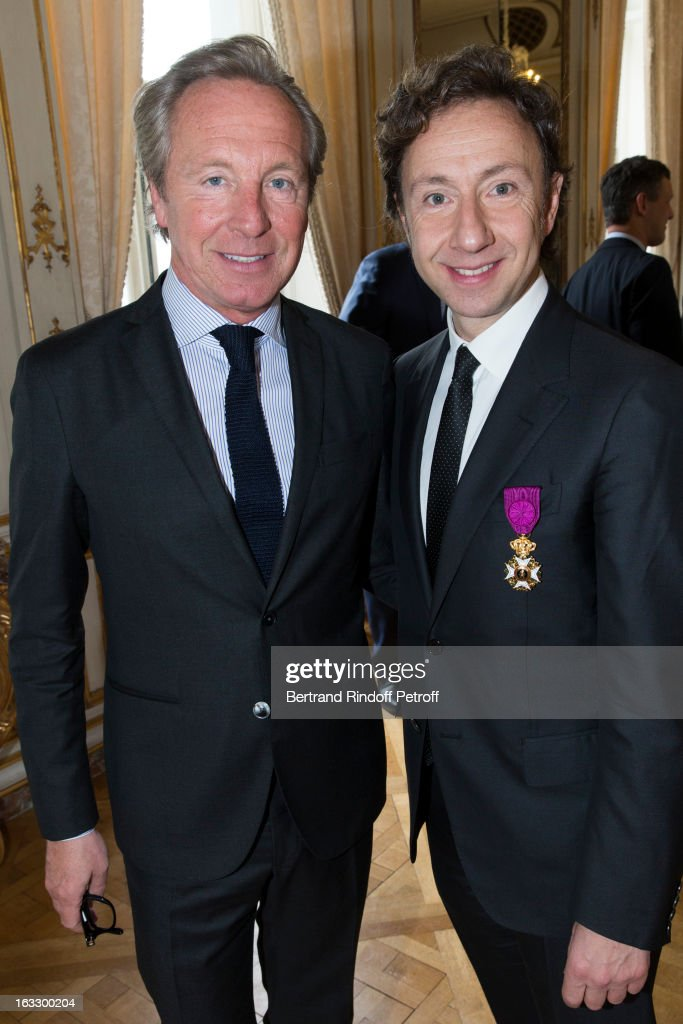 French journalist and author Stephane Bern (R) and Belgian fashion designer Edouard Vermeulen pose after Bern was appointed officer in the King Leopold order during a ceremony at Palais d'Egmont on March 7, 2013 in Brussels, Belgium.