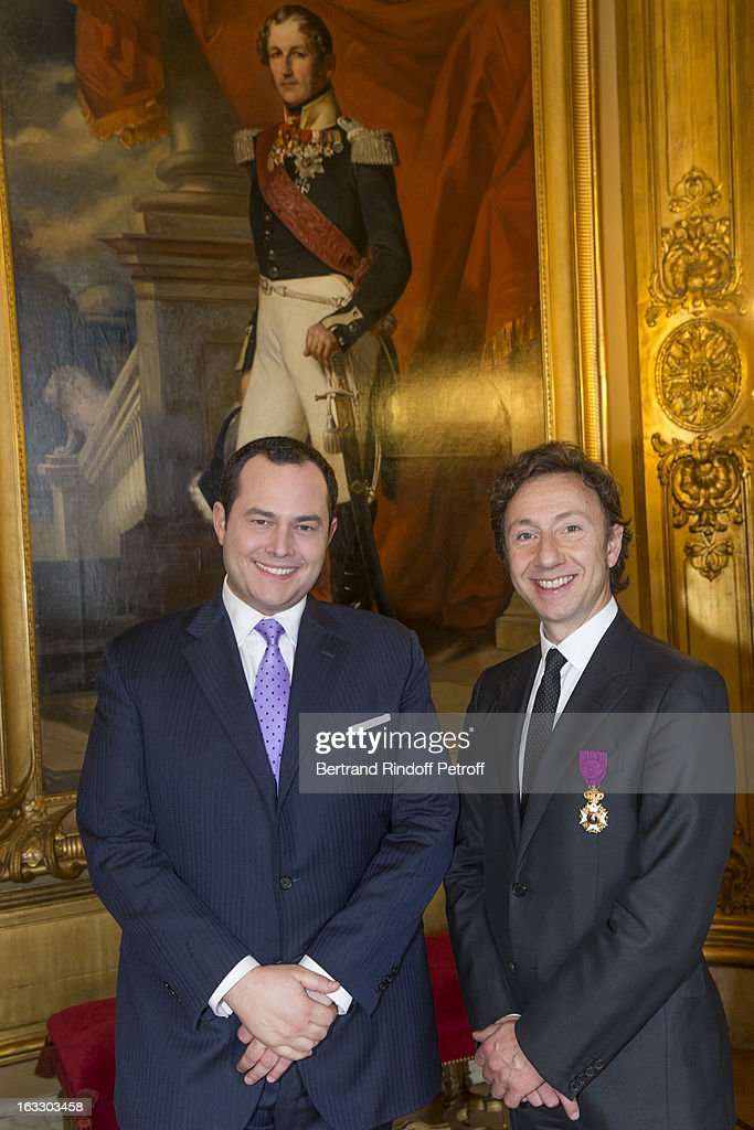 French journalist and author Stephane Bern (R) and Belgian reporter Thomas de Bergeyck pose by a painting of King Leopold I of Belgium after Bern was appointed officer in the King Leopold order during a ceremony at Palais d'Egmont on March 7, 2013 in Brussels, Belgium.