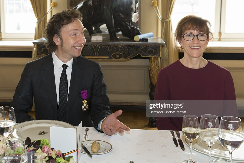 French journalist and author Stephane Bern (L) and Bernadette reynders, wife of Belgian Foreign Minister and Vice Prime Minister Didier Reynders, prepare to share a meal with guests after Bern was appointed officer in the King Leopold order during a ceremony at Palais d'Egmont on March 7, 2013 in Brussels, Belgium.