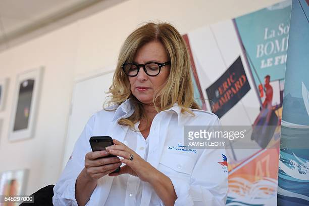 French journalist and former first lady of France Valerie Trierweiler looks at her mobile phone during the Solitaire du Figaro sailing race off the...