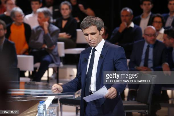 French journalist and TV host David Pujadas checks his notes before the start of the political TV show 'L'emission politique' on May 18 2017 on a set...