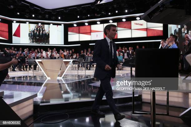 French journalist and TV host David Pujadas walks before the start of the political TV show 'L'emission politique' on May 18 2017 on a set of French...