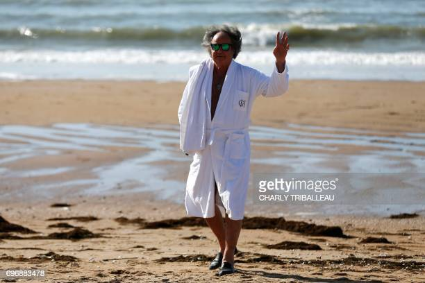 French journalist and writer Gonzague Saint Bris waves as he walks on the beach on June 16 2017 during the Cabourg Romantic Film Festival in Cabourg...