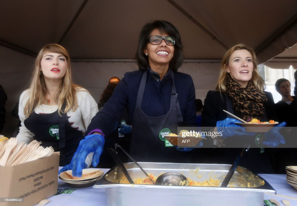 French journalist Audrey Pulvar (C), TV host Aude Pepin (L) and French journalist and TV host Elisabeth Bost (R) serve food during an event to raise awareness of the food waste on October 13, 2012 at the Place de l'Hotel de Ville in Paris. Five thousand people were invited to enjoy a giant curry prepared using 800 kg of twisted carrots and uncalibrated vegetables that supermarkets refuse to buy from producers and which usually end in disposal. 'While one billion people suffer from malnutrition in the world, a third of the food produced ends up in the trash! I am green since I was 4 years' said Stuart.