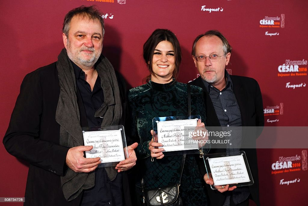 French journalist Denis Robert, his daughter French film director Nina Robert and French producer Bertrand Faivre pose with nomination certificates for the Cesar Award for Best Documentary for 'Cavanna, He was Charlie' during the nominations event for the 2016 Cesar film awards in Paris on February 6, 2016. The 41st Ceremony for the Cesar film award, considered as the highest film honour in France, will take place on February 26, 2016. / AFP / FRANCOIS GUILLOT