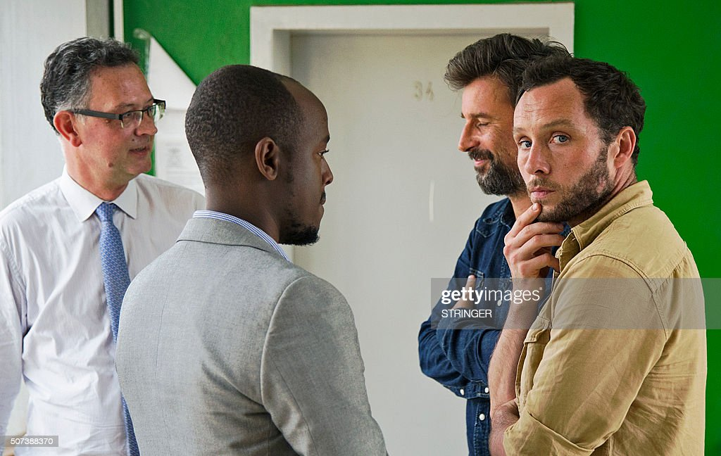 TOPSHOT French journalist for Le Monde newspaper Jean Philippe Remy and British freelance photographer Phil Moore speak with the French Ambassador to...
