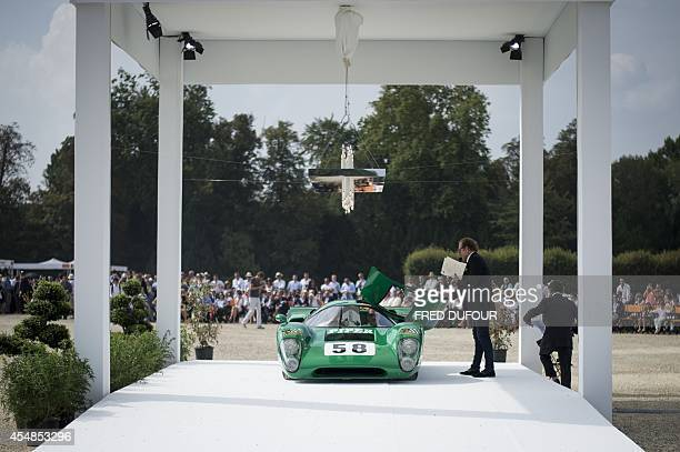 French journalist Guillaume Durand stands by a 1969 Lola T70 Mk III B race car during the first edition of the Chantilly Arts and Elegance Richard...