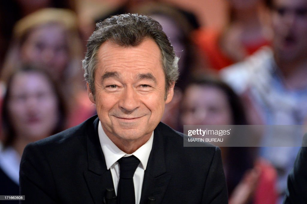 French journalist Michel Denisot smiles on the set of French TV Canal+ talk show 'Le Grand Journal,' he anchored for the last time on June 27, 2013 in Paris. AFP PHOTO / MARTIN BUREAU BUREAU