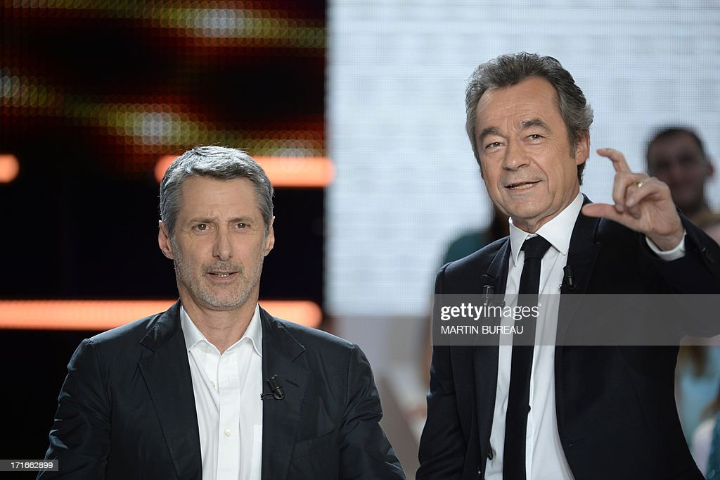 French journalist Michel Denisot (R) stands by his successor Antoine de Caunes on the set of French TV Canal+ talk show 'Le Grand Journal,' he anchored for the last time on June 27, 2013 in Paris.