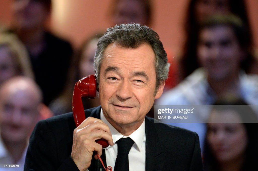 French journalist Michel Denisot takes part in a sketch on the set of French TV Canal+ talk show 'Le Grand Journal,' he anchored for the last time on June 27, 2013 in Paris.