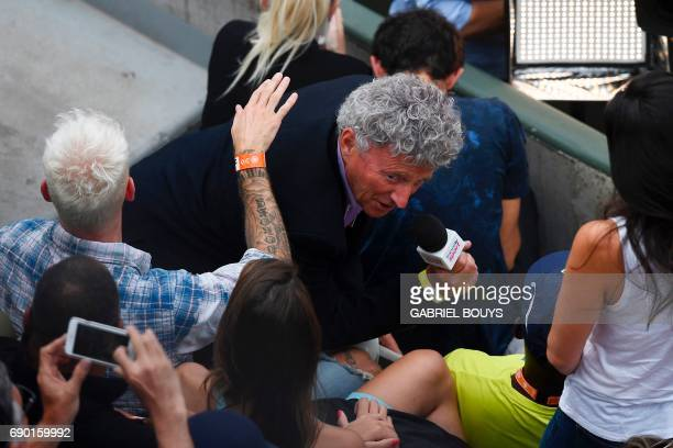 French journalist Nelson Monfort holds his mic next to French singer M Pokora during a tennis match at the Roland Garros 2017 French Open on May 30...