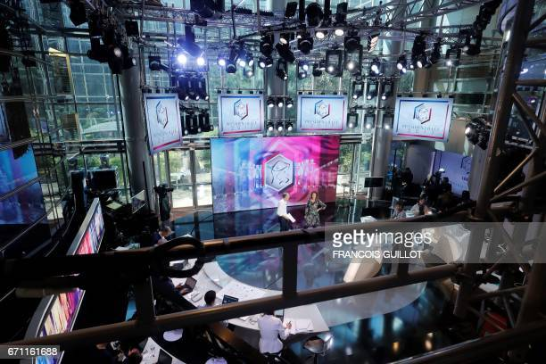 French journalists Gilles Bouleau and AnneClaire Coudray stand on the set of the French TV channel TF1 on April 21 2017 in a BoulogneBillancourt near...
